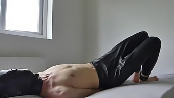 Submissive In Bondage Hood And Handcuffs On Bed